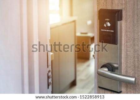 Electronic knob door handle with open door in front of hotel room. Conceptual of electronic doorway in front of hotel, resort or condominium etc. #1522858913
