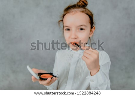 Little business lady Business lady on a gray background. The business lady is seriously and surely paints her lips. Formal fashion for a small business lady #1522884248