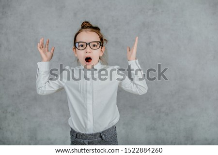 little businesswoman. little businesswoman on grey background. business lady. little businesswoman with serious and confident look. formal fashion for little businesswoman. Hold hands up. #1522884260