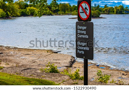 A bilingual sign warns people not to swim in the river due to the danger of strong currents. #1522930490