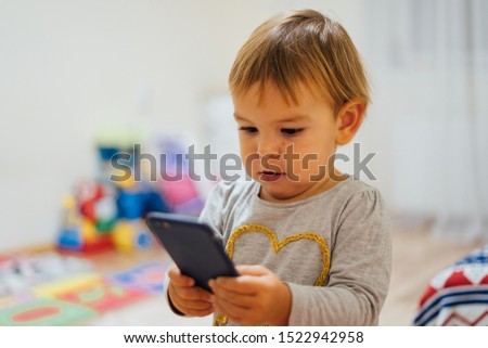 Baby using phone, playing game or watching cartoons. Home indoors. Screen time