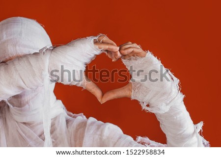 Halloween, costume image. The mummy's hand in bandages making gestures. Love you, sweet mummy shows heart sign by hands