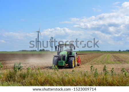Tractor busy ploughing the field #1523009714