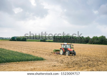 Tractor busy ploughing the field #1523009717