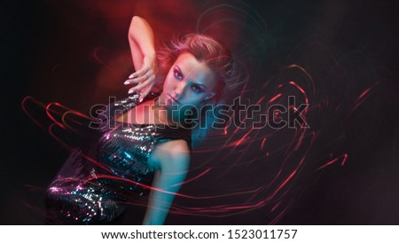 Attractive dancing blonde in the club, neon light, motion effects. Black background, long exposure #1523011757
