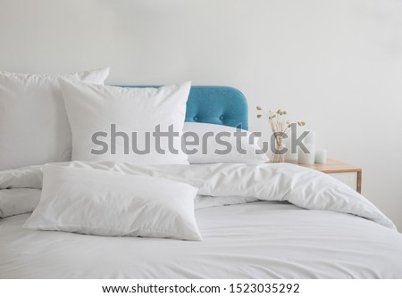 White pillows, duvet and duvet case on a blue bed. White bed linen on a blue sofa. Bedroom with bed and bedding. Messy bed. Front view. #1523035292