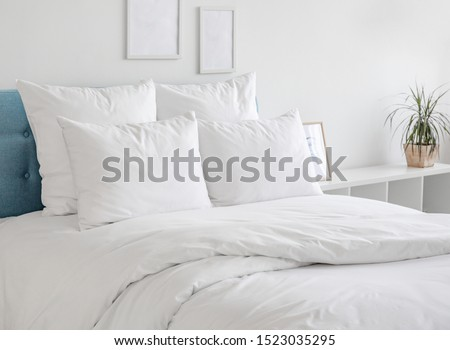 White pillows, duvet and duvet case on a blue bed. White bed linen on a blue sofa. Bedroom with bed and bedding and poster frame mock up on the wall. Left side view. #1523035295