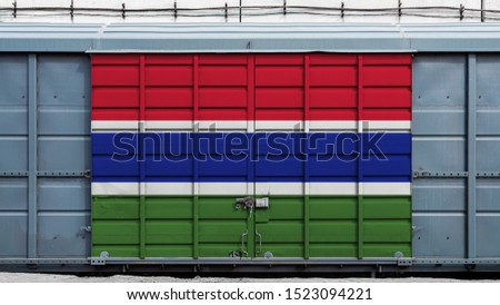 Front view of a container train freight car with a large metal lock with the national flag of Gambia.The concept of export-import,transportation, national delivery of goods and rail transportation #1523094221