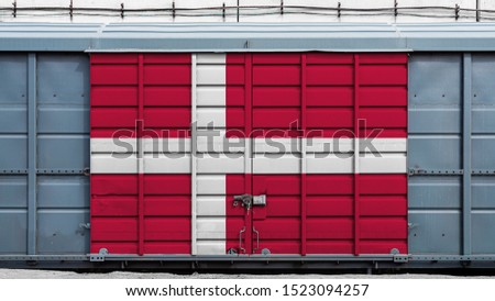 Front view of a container train freight car with a large metal lock with the national flag of Denmark.The concept of export-import,transportation, national delivery of goods and rail transportation #1523094257