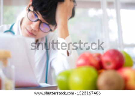 Blurred background. Nutritionist studying on fruit supplements in hospital. Nutritionist doctor/ food specialist consider program for patients diet & lifestyle. Weight loss & healthy eating concept.   #1523167406