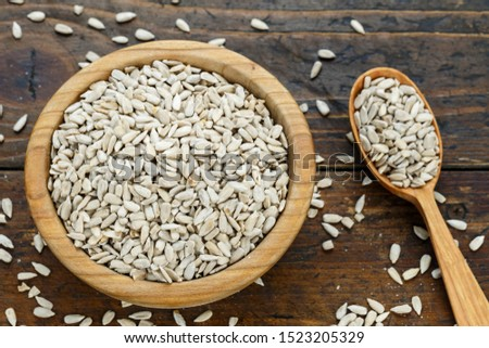 peeled sunflower seeds in a wooden plate on a wooden background. place for text