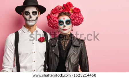 Bridal couple celebrate typical Mexican holiday, wear special costumes, have wedding on cemetery, pose indoor against pink background, blank space aside. Day of Dead carnival and celebration. #1523214458