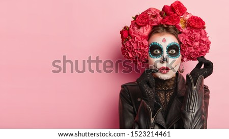Studio shot of lovely woman wears halloween makeup, dressed in black outfit, red wreath, has zombie image, looks with scaring expression, isolated over rosy background, free space for your promotion Royalty-Free Stock Photo #1523214461