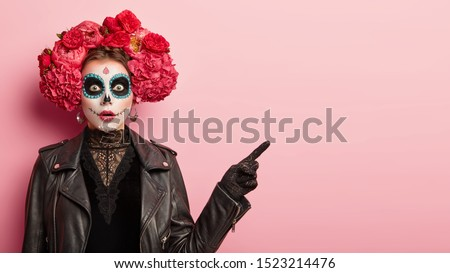 Studio shot of emotive gothic woman has image of horror dead woman, wears skull makeup, wreath around head and black leather jacket, points away, shows direction with stupor. Scarying girl indoor #1523214476