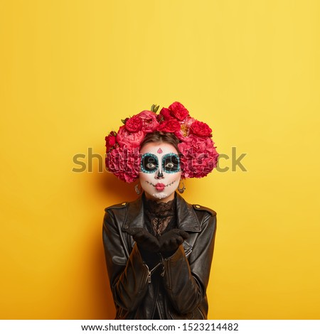 Portrait of female zombie with painted skull face, sends air kiss, expresses love, celebrates day of death, prays for family members who died comes on Mexican holiday or festival has halloween makeup #1523214482