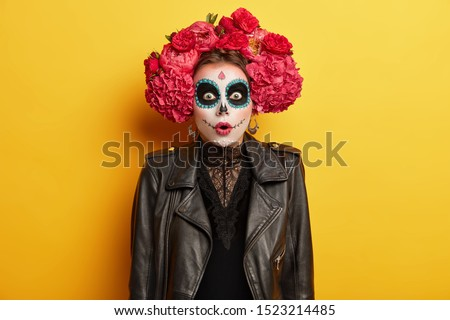 Stupefied terrified woman with ghost painted face, ready for dead parad in Mexico to honor died people, dressed in lace black dress, leather jacket, red flower made wreath stands over color background #1523214485