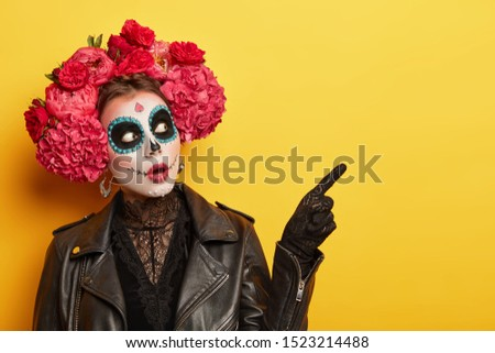 Terrified woman wears professional makeup for horror, dressed in black clothes, points away, wears gloves, red peonies wreath, celebrates Halloween holiday or Day of Death. Image of Calavera Catrina #1523214488