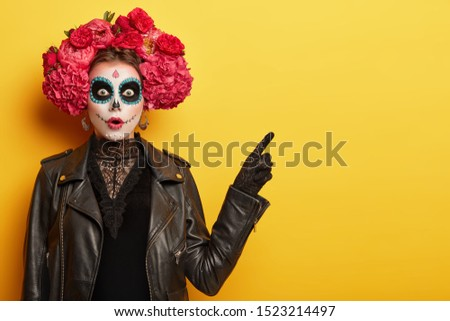 Surprised young woman has image of spooky ghost, has clay skull face, professional makeup wears red garland made of odorous flowers points away with scared expression invites going in mysterious place #1523214497