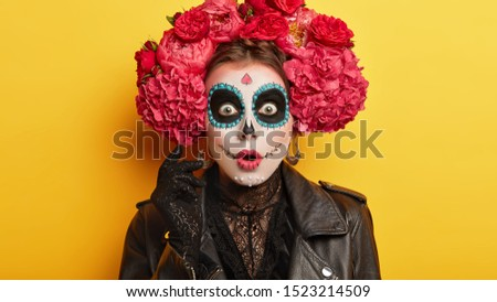 Horrified woman with painted skull on face, dressed in special costume during day of death to honour dead people, celebrates Mexican version of Halloween, holds breath from seeing something terrifying #1523214509