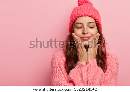 Studio shot of pleasant looking female model touches chin with both palms, has eyes closed, enjoys delicate well cared skin, has dark hair, dressed in winter outfit, isolated on pink wall, blank space #1523214542