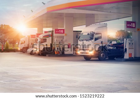 Trucks refueling in petrol station, Transportation vehicle, Business logistics, delivery transport, cargo logistic concept. Freight shipping, at sunset background. Royalty-Free Stock Photo #1523219222