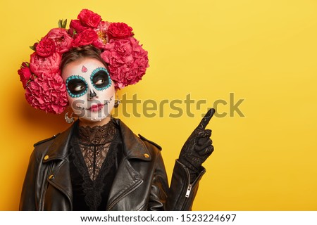 Face art and traditional Mexican holiday concept. Serious young lady wears dead mask skull makeup, flower wreath with strong scent to guide souls from cemetries, points on free space over yellow wall #1523224697