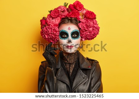 Female participant of Mexican holiday has professional makeup, resembles skull to honor dead relatives has black eyes wears red peonies wreath dressed as spirit models indoor over vivid wall #1523225465