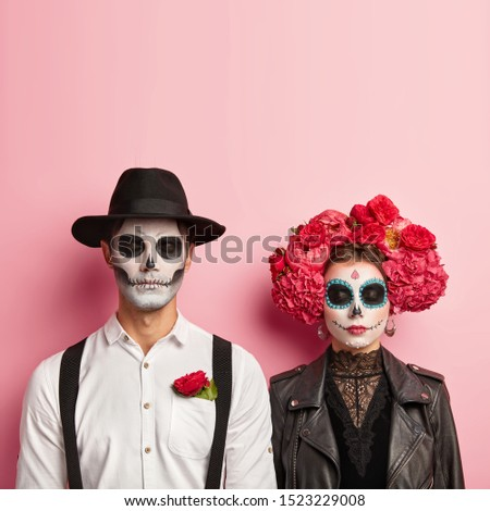 Lovely couple wear zombie costume for Halloween, have skull makeup, man wears hat and white shirt with red rose in pocket, woman in black leather jacket and flower wreath, wait for party together #1523229008