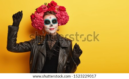 Pleased female has mysterious image, wears black lace dress and gloves, dances during halloween party, has professional painted face resembles skulls, has flower wreath on head. Mexican Day of Death #1523229017