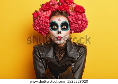 Portrait of female dapper skeleton prepares for Mexican carnival, blows air kiss, wears skull makeup, dressed in black jacket, has scary look, isolated over yellow background. Bodypaint and face art #1523229020