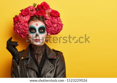 Photo of young woman has face arfully painted to resemble skulls, wears black leather jacket and gloves, wears garland made of red aromatic flowers, supports spiritual journey of dead people #1523229026