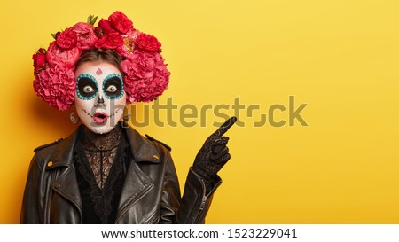 Happy Halloween concept. Scared horrible female in special outfit, wears white clay skull, professional makeup to look spooky, wears black clothes points away on blank space against yellow background #1523229041