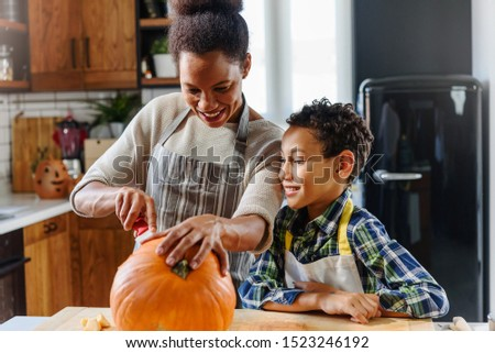 Mother and son carving pumpkin making Jack-o-Lantern Royalty-Free Stock Photo #1523246192