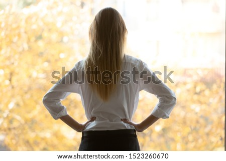 Rear view thoughtful millennial business woman looking at office window. Puzzled young female team leader put hands on waist, lost in thoughts, solving problems or thinking about opportunities. Royalty-Free Stock Photo #1523260670