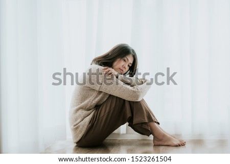 Sad Asian woman with depression sitting alone on the floor. major depressive disorder #1523261504