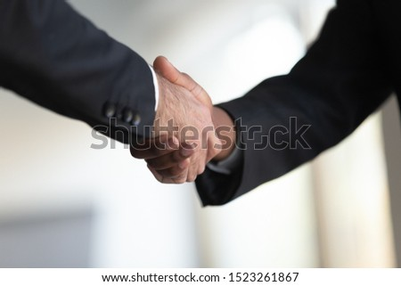 Close up two mixed race businessmen in suits shaking hands at office. Company boss celebrating contract signing with african american corporate client or investor. Male business partners making deal.