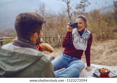 Gorgeous smiling Caucasian brunette sitting on blanket and taking picture of her boyfriend and dog. Picnic at autumn concept.