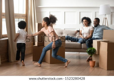 Overjoyed african american curly kids playing, catching each other near cardboard boxes with belongings while happy black parents embracing, relaxing on couch in new renovated living room. #1523280428