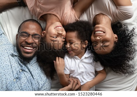Smiling african american family of four lying on bed head to head with closed eyes, happy parents relaxing with kids elder girl and smaller boy on bed, enjoying weekend leisure free time spending. #1523280446