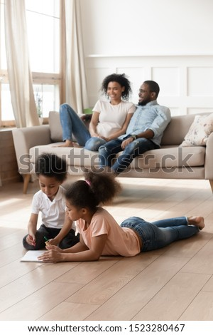 Mixed race older girl and preschool boy laying on warm floor, coloring pictures while happy parents relax on couch. Elder sister teaching small brother, helping drawing, playing, having fun together.