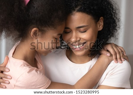 Close up smiling happy mixed race little girl embracing mum or babysitter, touching foreheads, holding, hugging each other, young woman hug small adopted daughter, bonding with closed eyes #1523280995