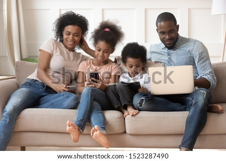 Happy digital tech african american family using electronic gadgets, holding smartphones, tablet, computer, sitting together on sofa, smiling mom, dad and kids having fun with devices, ecommerce. #1523287490