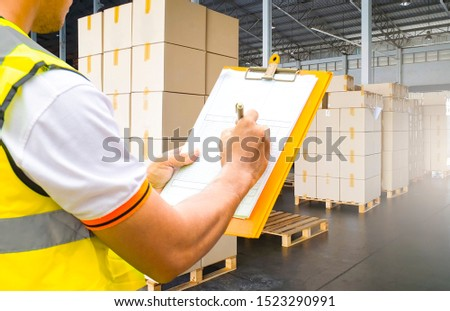 warehouse worker hand holding clipboard inspecting checklist of goods shipment at distribution warehouse, stack cardboard boxes on wooden pallets, warehouse inventory management, logistics transport #1523290991