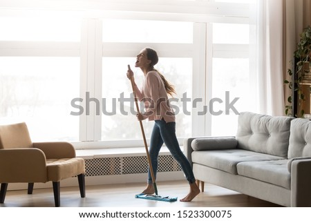 Funny happy young woman holding mop microphone singing song in modern living room interior with big window, carefree active funky girl having fun cleaning floor at home enjoying housework alone #1523300075