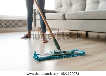 Woman housewife wash wooden laminate floor in modern living room, female cleaner housekeeper maid holding mop cleaning at home, domestic housework professional household service concept close up view  #1523300078