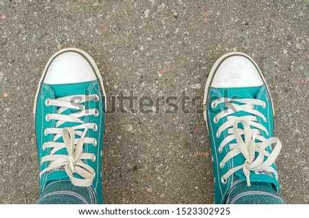 sneakers on the asphalt road. Space for editorial use. Top view of old sneaker shoes on a gray sidewalk asphalt background. Man standing on grunge asphalt city street, perspective perspective #1523302925