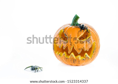 Big orange pumpkin with eyes and mouth and two spiders, isolated on a white background. Halloween concept. #1523314337