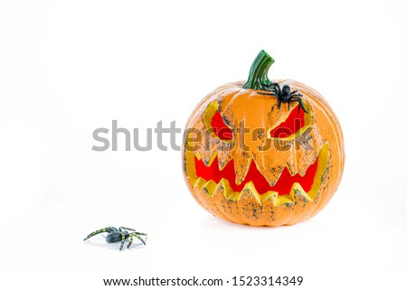 Big orange pumpkin with eyes and mouth with red light, and two spiders, isolated on a white background. Halloween concept. #1523314349