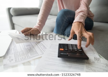 Woman renter holding paper bills using calculator for business financial accounting calculate money bank loan rent payments manage expenses finances taxes doing paperwork concept, close up view #1523326748
