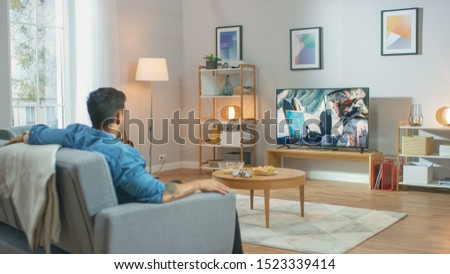 In the Living Room: Guy Relaxing on a Couch Watching War Movie on a TV. Modern Military Warfare Action with War Soldier Shown on a Television. #1523339414